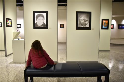 Student looks at the K-12 Art Show in the HUB Robeson Gallery.