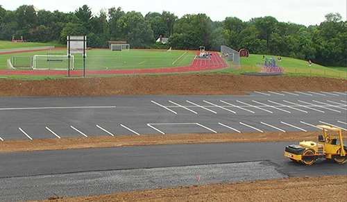 aerial view of parking lot being paved in front of the high school track